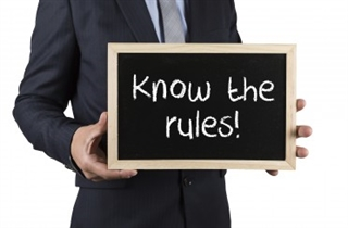 "man holding sign with ""know the rules"" written"